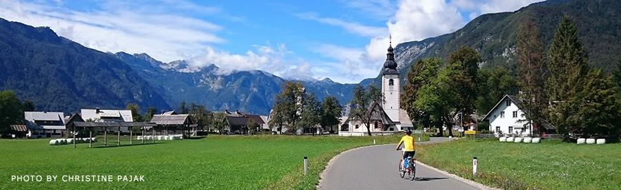Cyclist approaching alpine village with a church