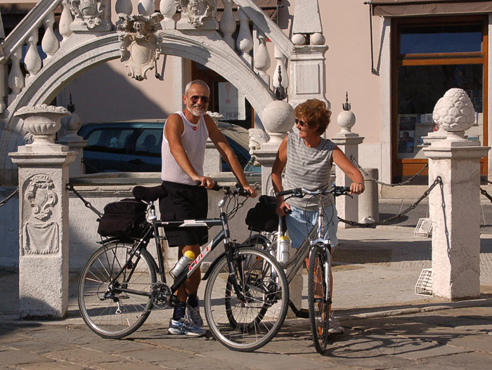 older couple on bikes in an old town