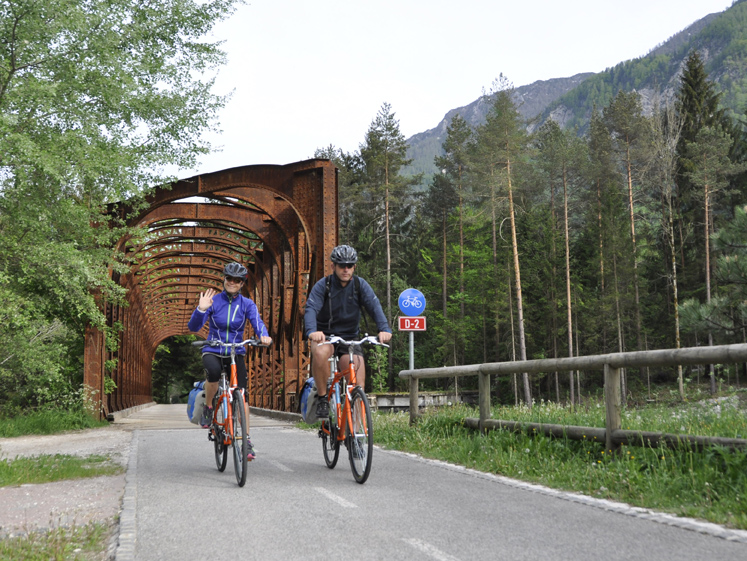 two cyclist riding bike from a bridge